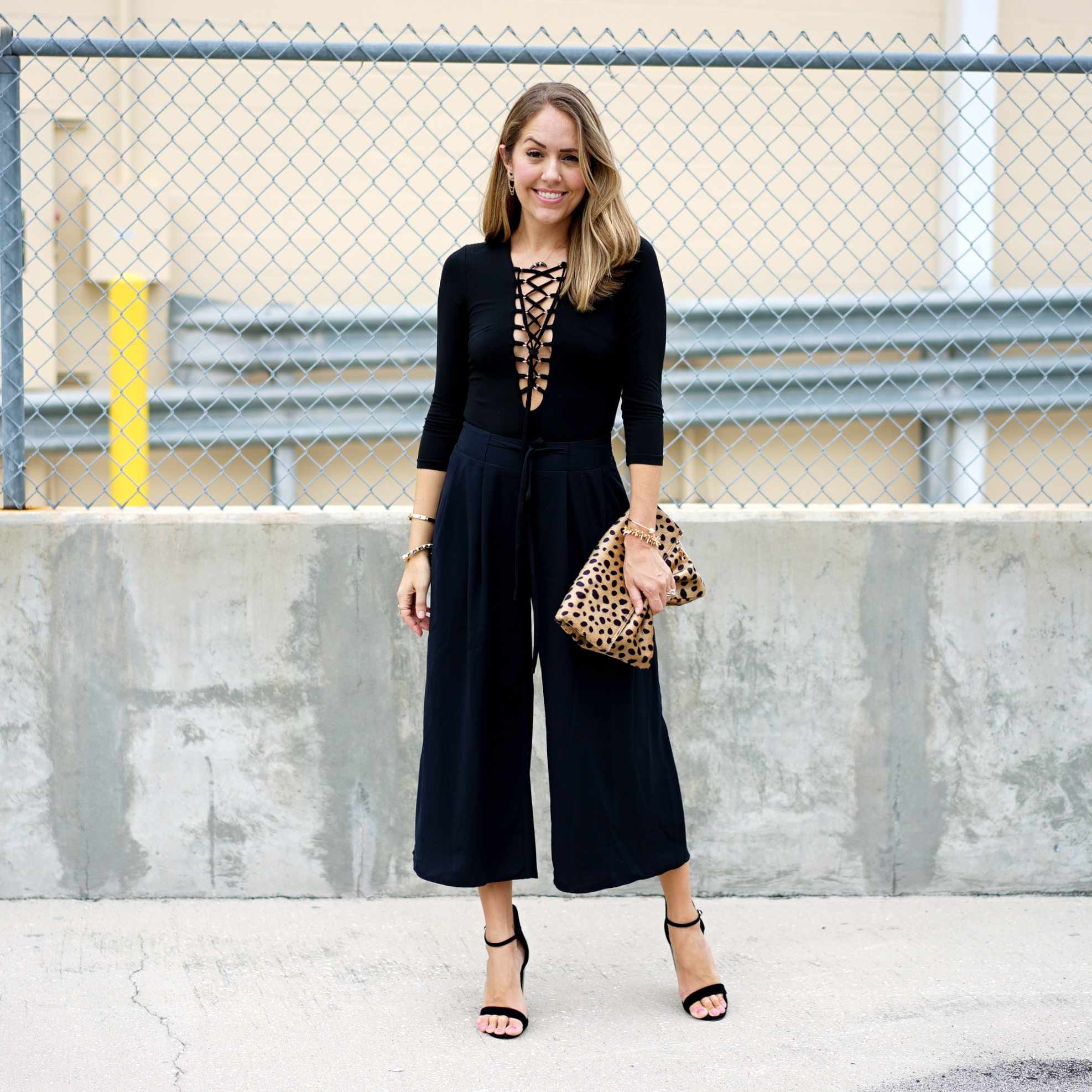 Lace up bodysuit and black culottes with leopard clutch
