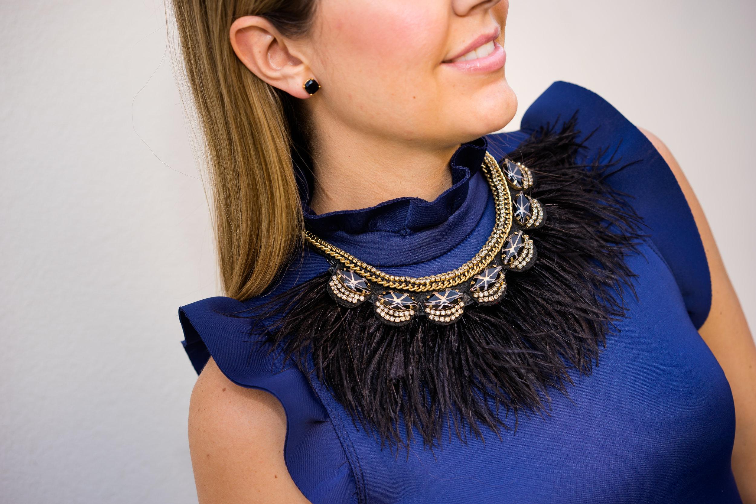 Navy dress, black feather necklace
