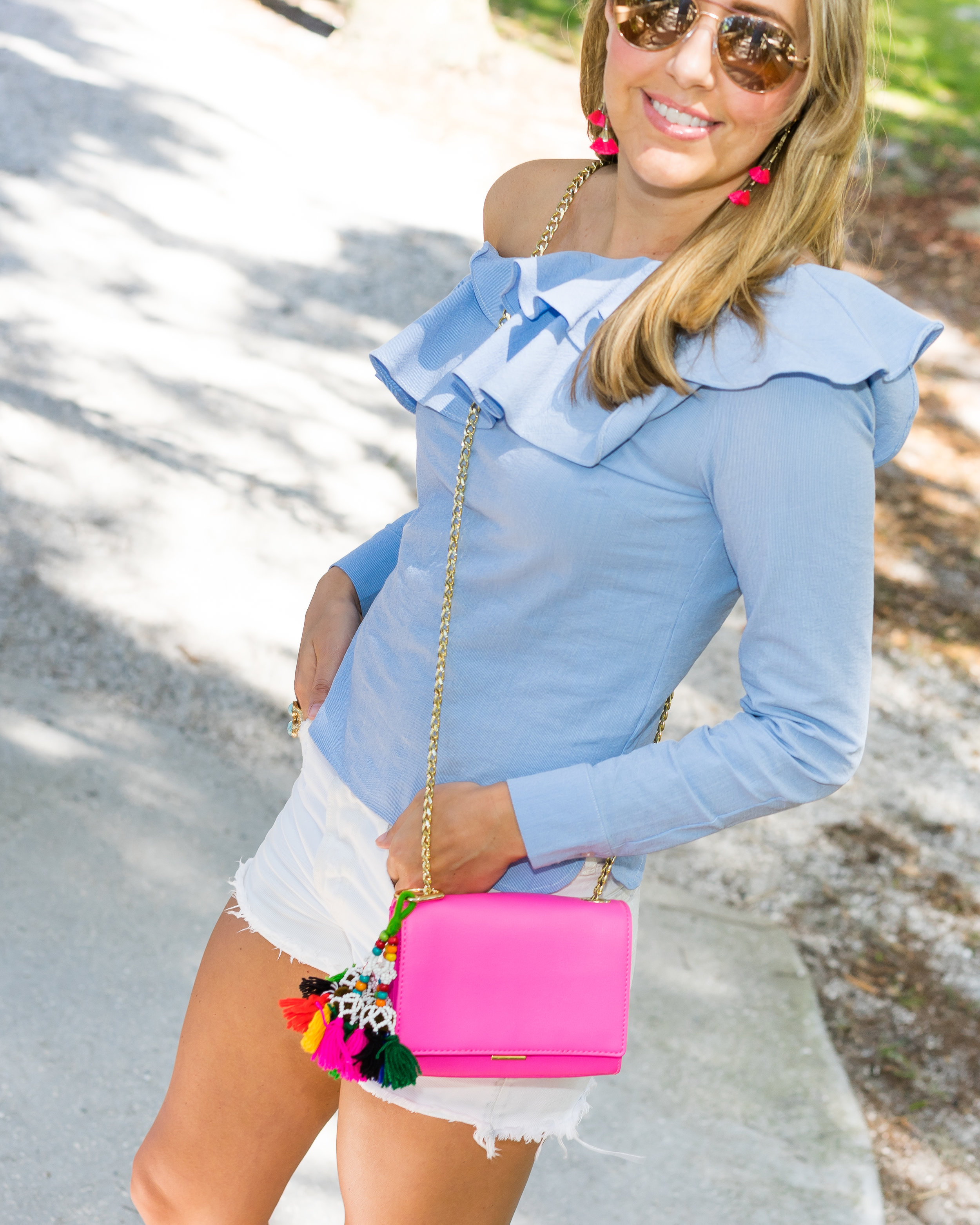 Blue ruffle top with white shorts, pink purse