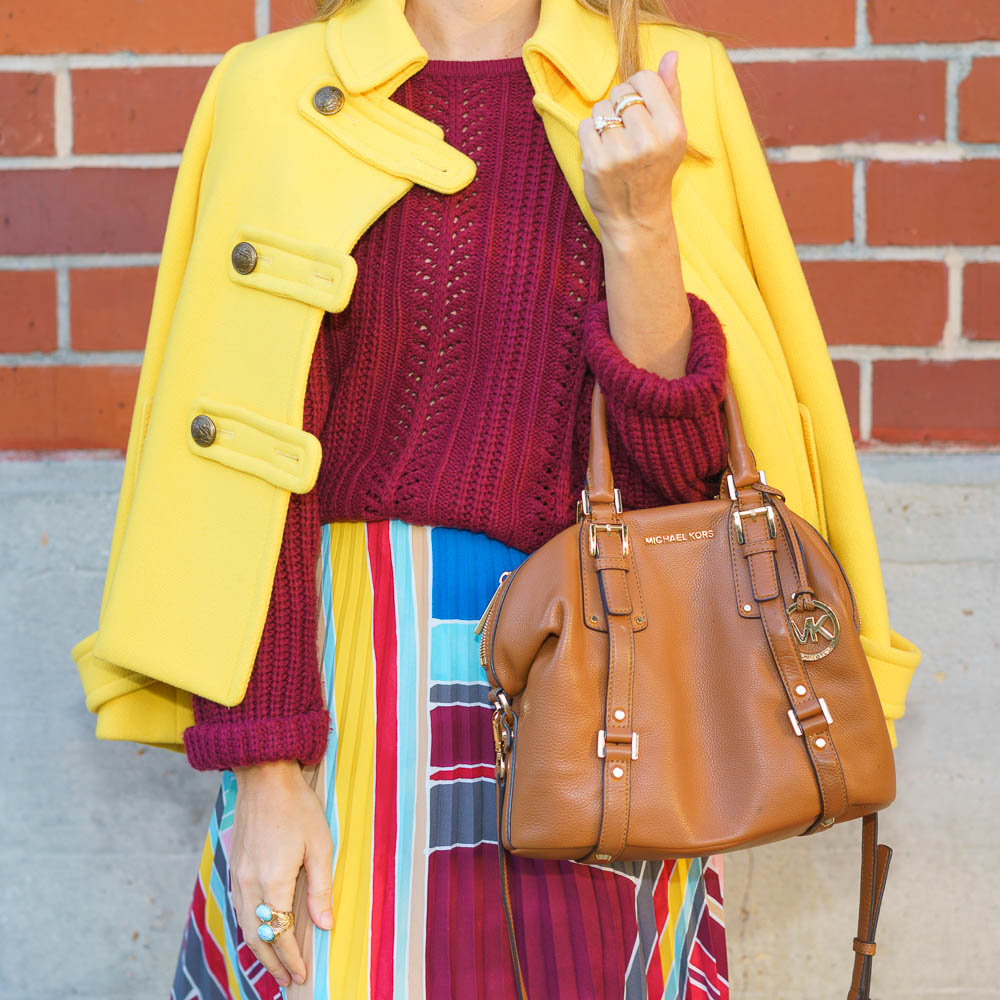 Colorful winter outfit: yellow coat, pleated skirt, burgundy sweater