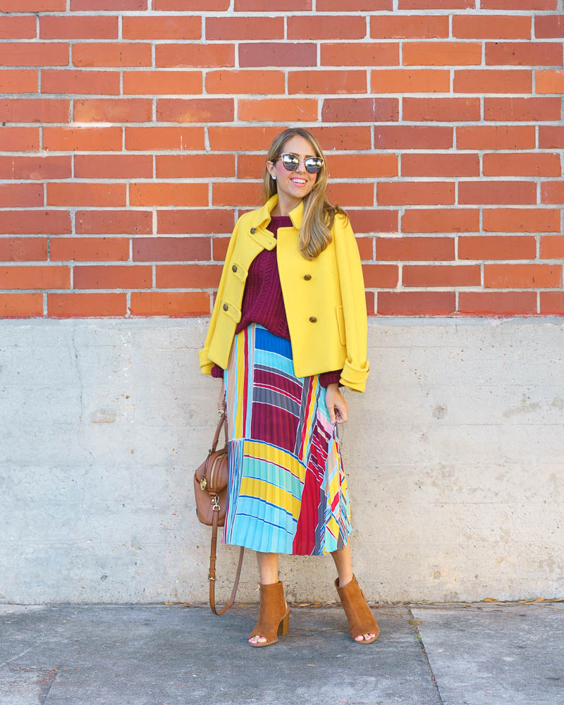 Colorful winter outfit: yellow coat, pleated skirt