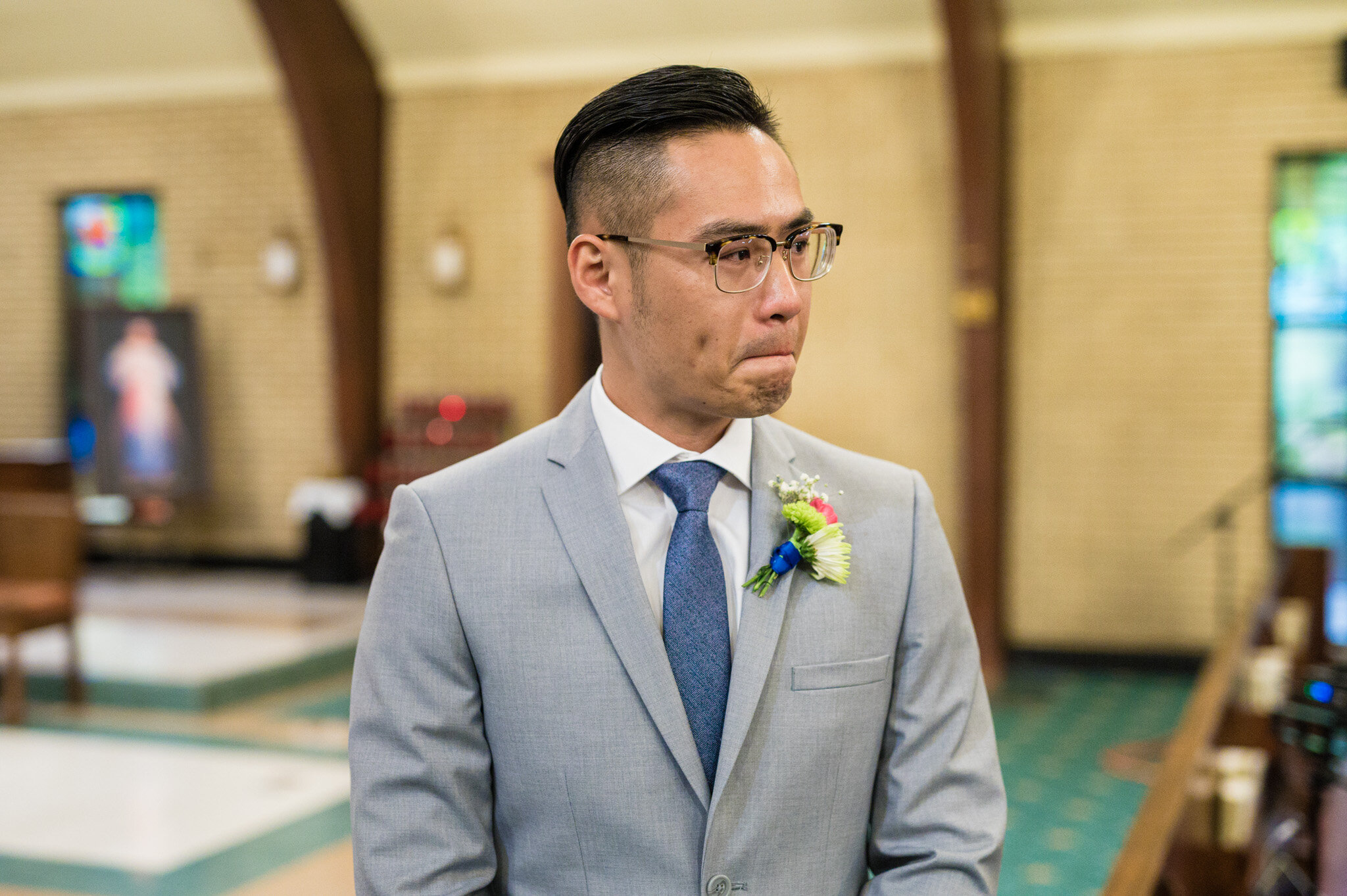 A groom's emotional reaction to seeing his bride walking down the aisle