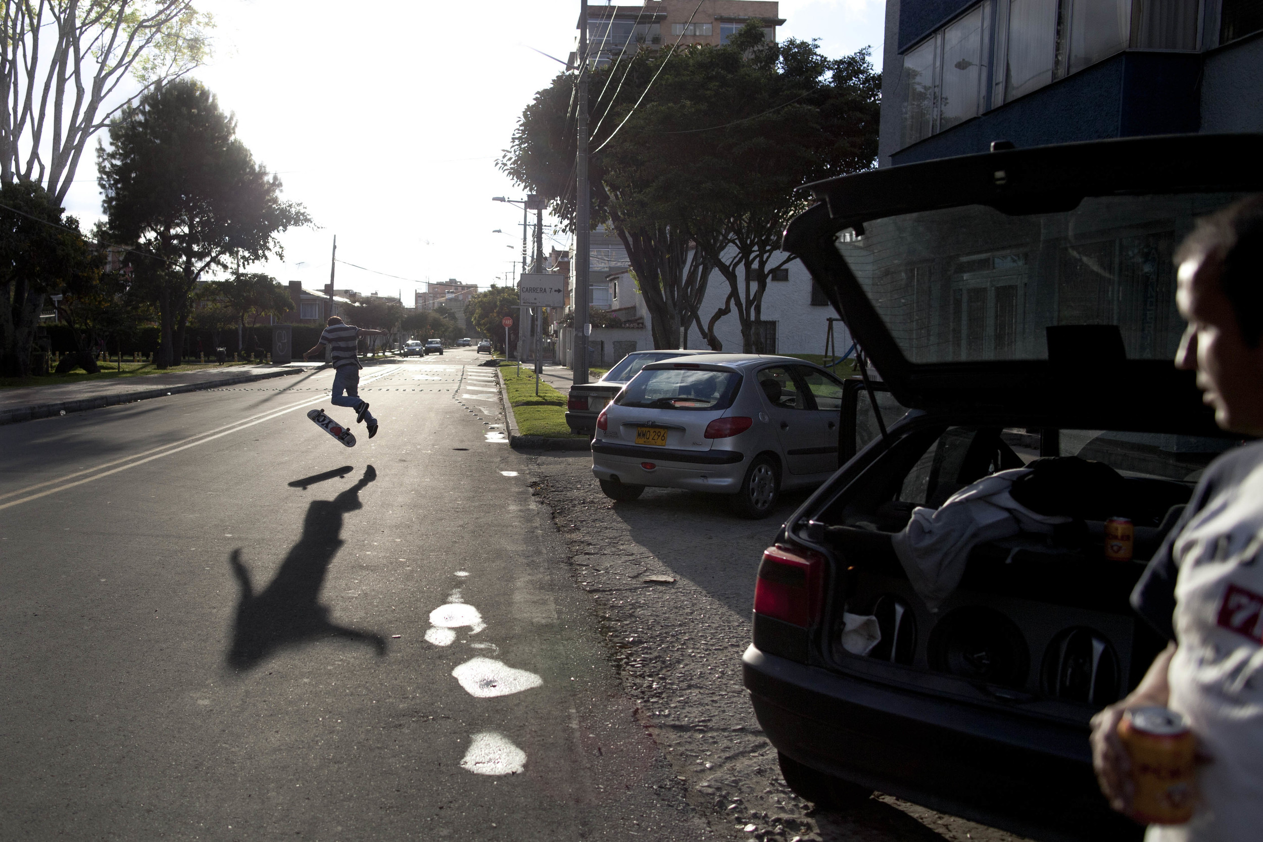 Bogotá. 22 July 2012. Felipe skateboarding on a road close to his home in Bogotá while being watched by his dad Alvaro.