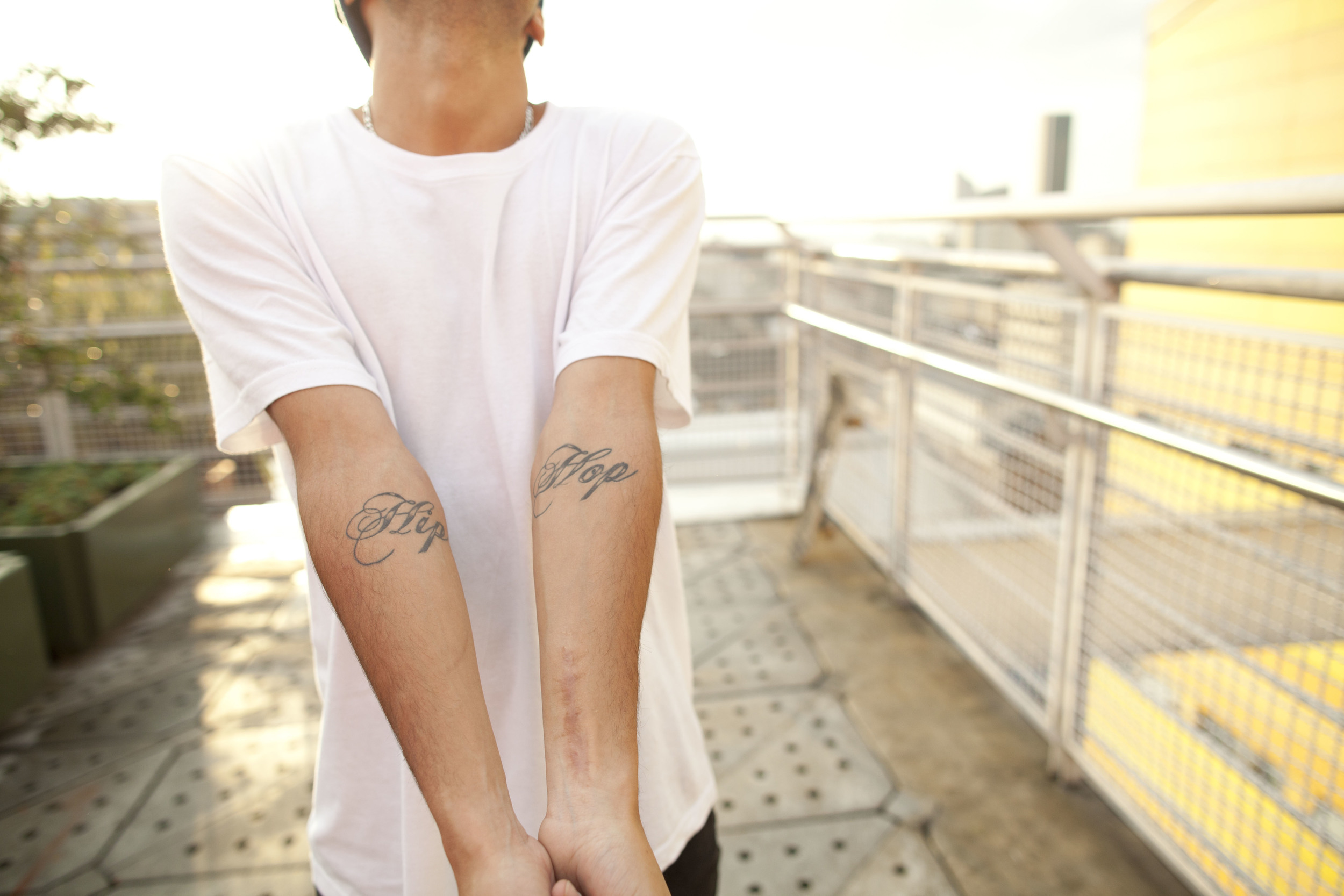 Bogotá. 3 August 2012. Felipe's arm marked by a scar from a previous skateboarding accident and a tattoo saying 'Hip Hop'.