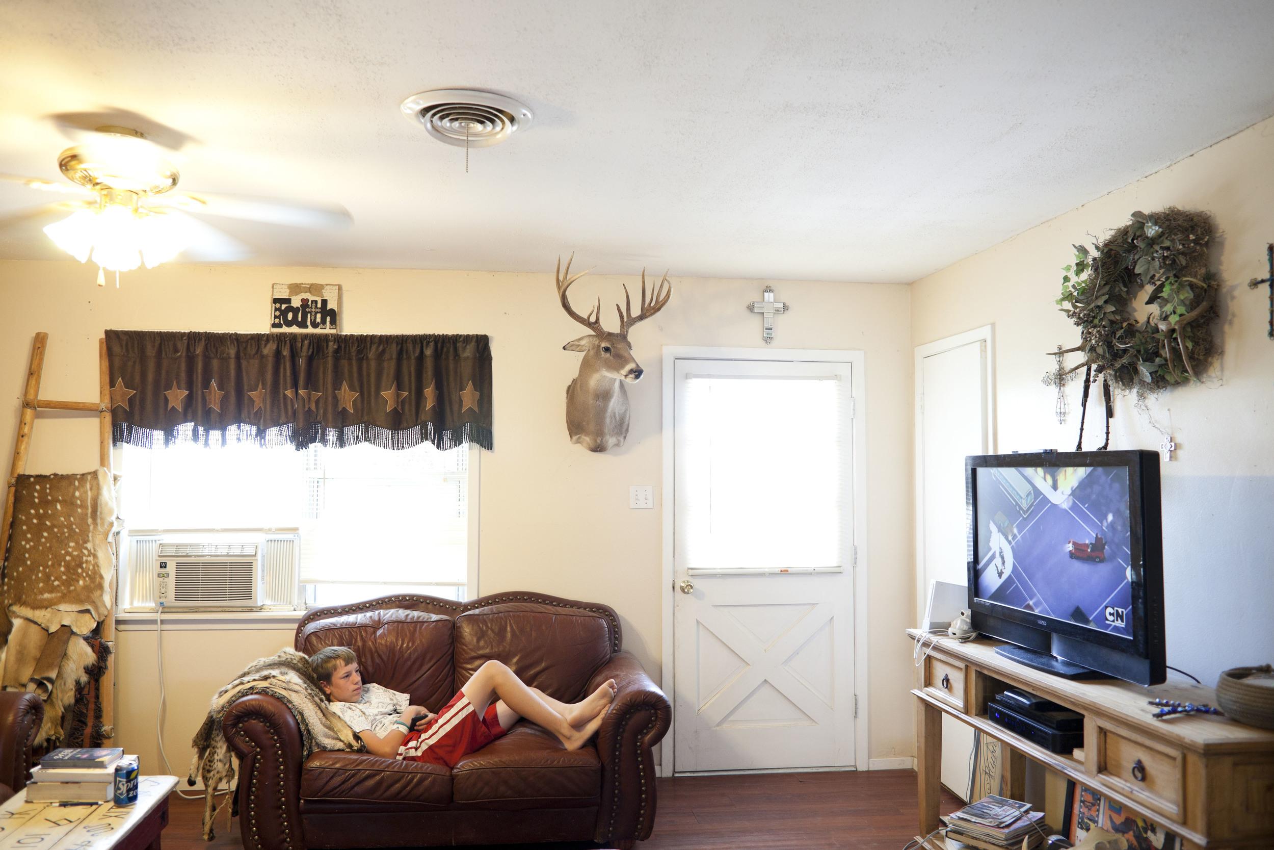 USA. Texas. Marfa. August 2013. Clayton Kibbe watching TV.