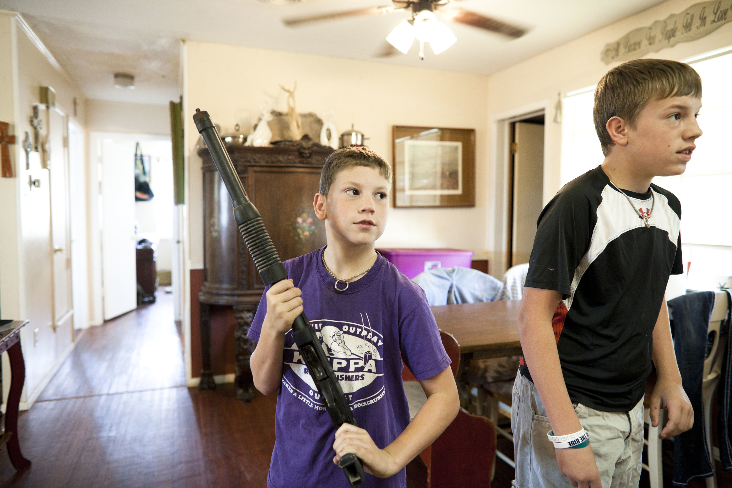 USA. Texas. Marfa. August 2013. 9-year-old Wyatt Kibbe presenting his rifle during breakfast.