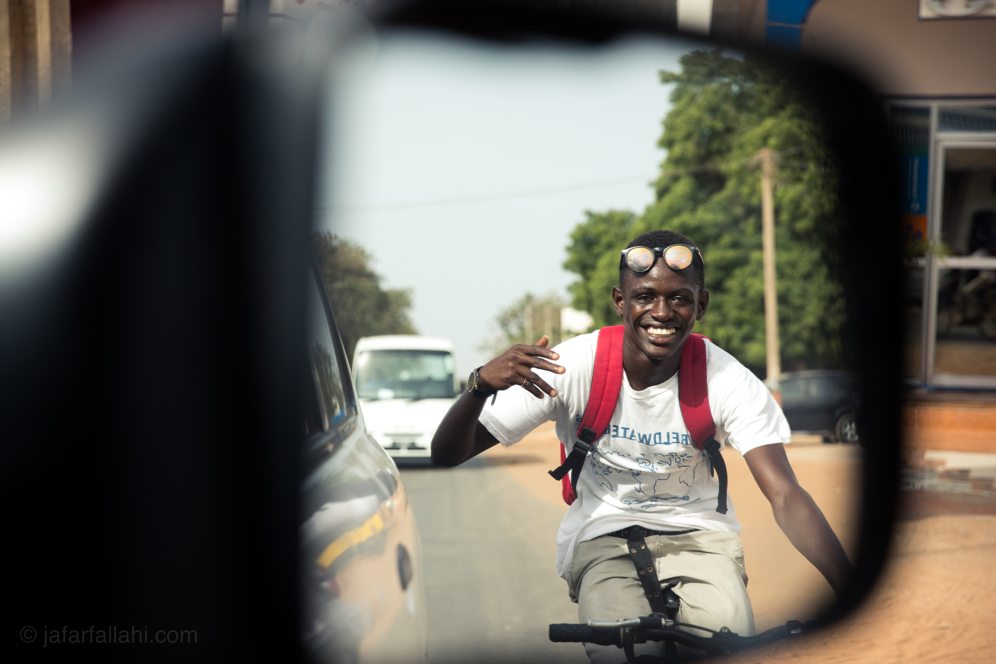 This guy was using our truck to tow him around town. As soon as he saw me taking his picture through the rear-view mirror he smiled and waved.