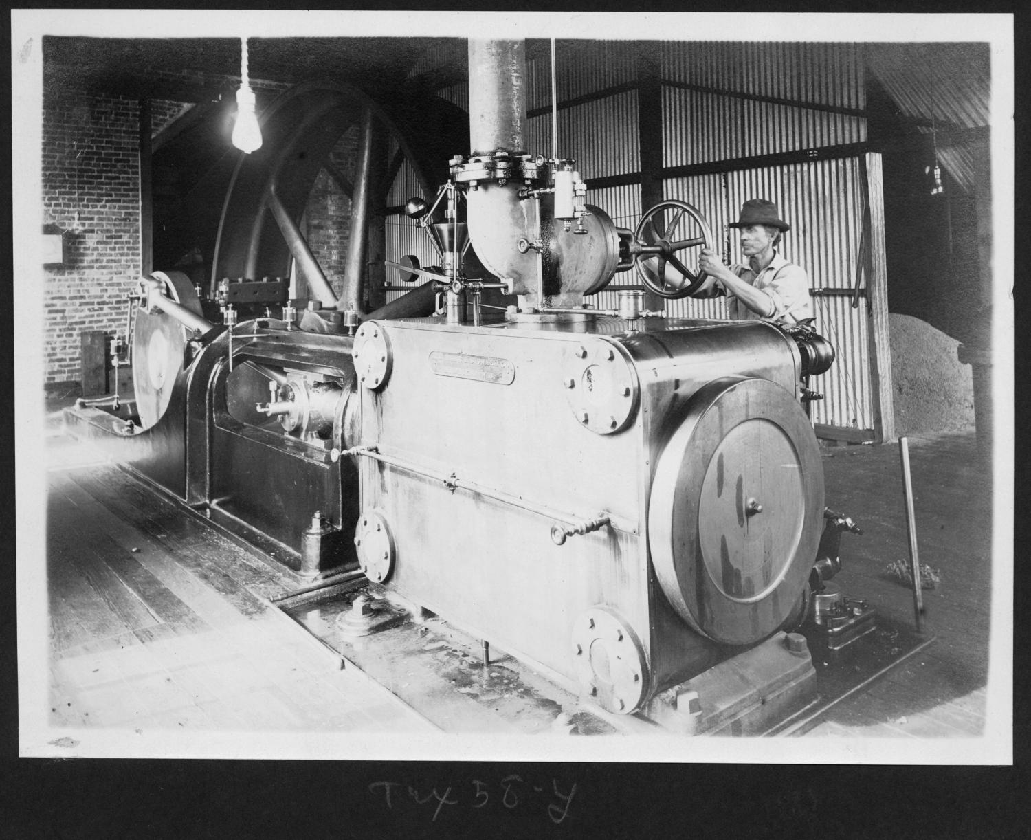 Tex58 Worker with Machinery Inside of the Mill