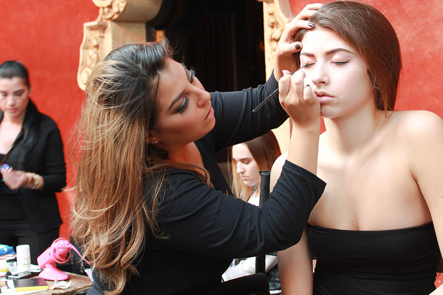 The pressure is on while Natalie re-applies black and gold eyeliner on her first model.