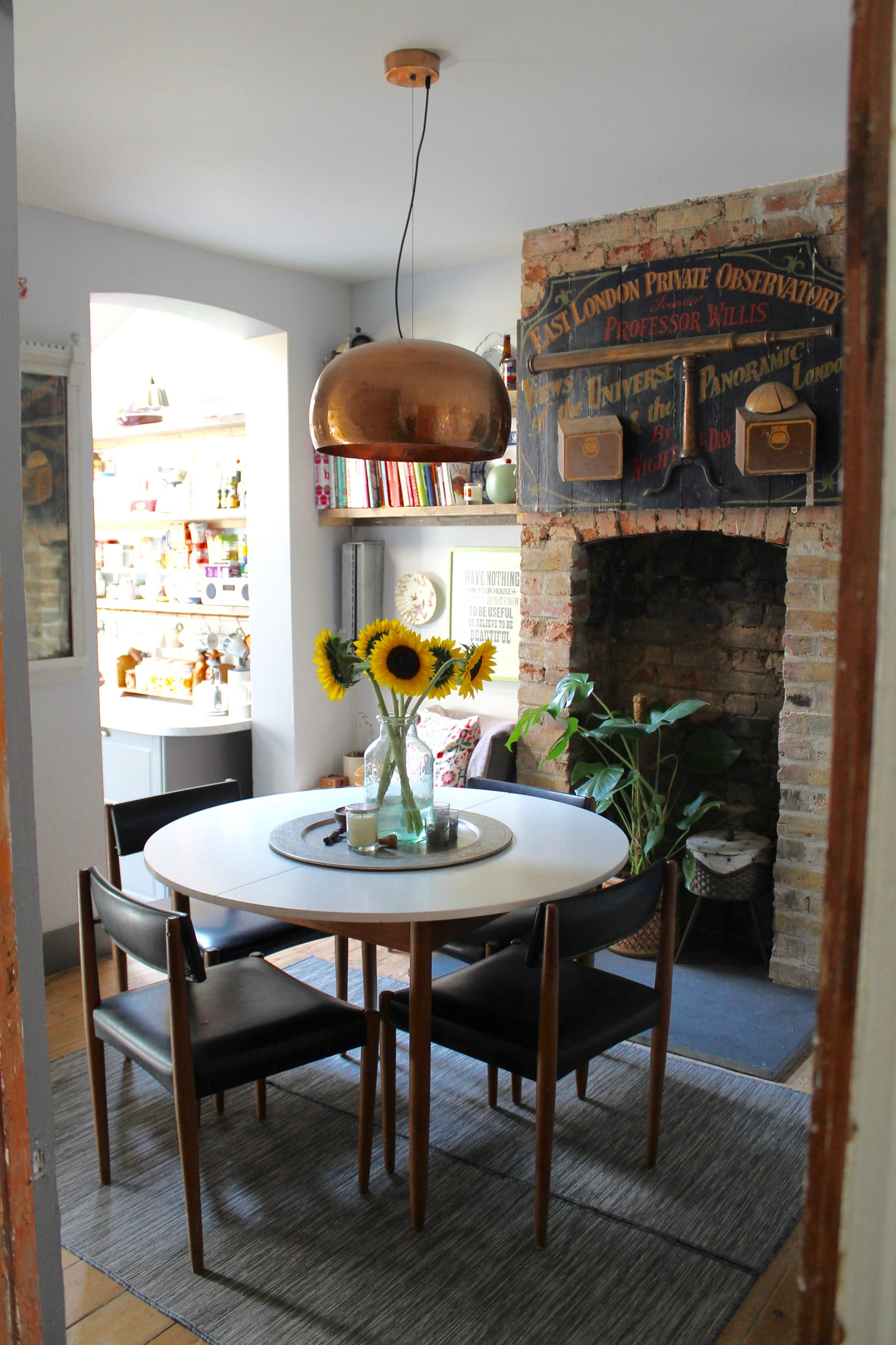 Photography provided by Joanna Thornhill - Dining room with my 1960's eBay table and chairs, IKEA rug and 3D artwork above the fireplace found on the street.
