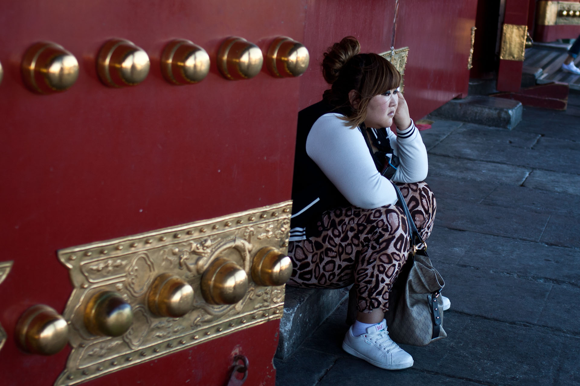 bored looking teenager at the gates of the forbidden city. probably being dragged round on one of the popular Chinese cultural tours of the city.