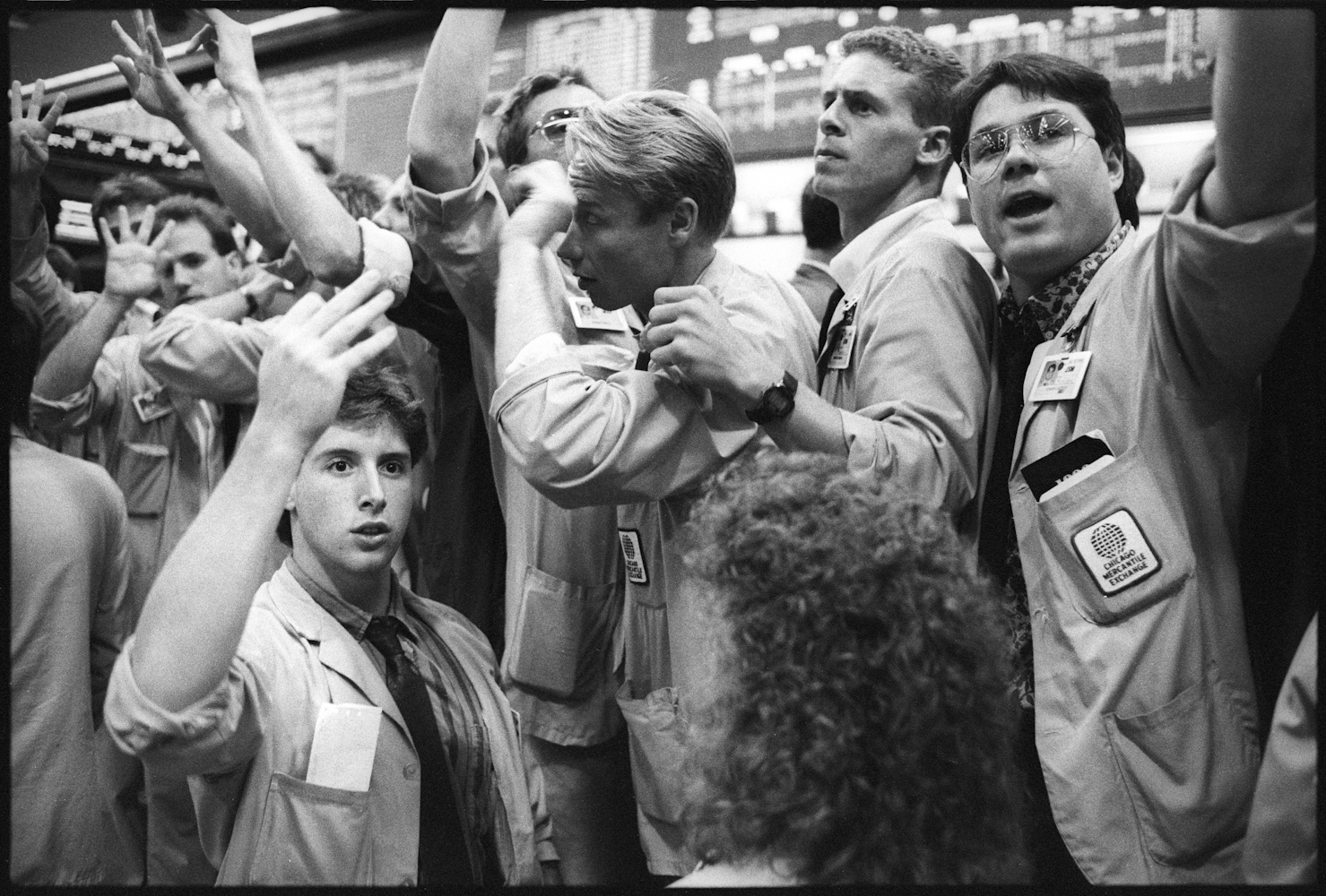 Traders on the floor of the Chicago Mercantile Stock Exchange using hand signals and yelling to trade commodities.