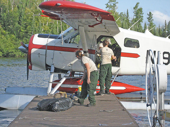Photo: Sara Schoonover (left) and Ali  Tetrick unloaded supplies after being flown to an inaccessible area near  the Knife Lake fire.