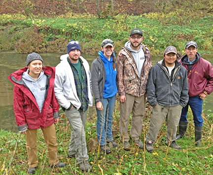 Photo: Corps members Bethany Dahl, Drew Wilwert, Jennie LaRoche, Travis Wilder and Joe McCarthy with Rich Stemper of the Root River SWCD stand on the banks of Riceford Creek in Spring Grove, which they stabilized using tree revetments.