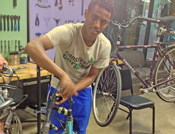 Photo: Dima Iresso from the YO3 crew repaired a bike during his crew's spring service project at Cycles for Change.