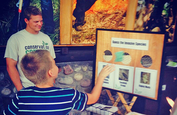 Corps member Joseph Bauman helped a young fairgoer play the invasive species game while volunteering at the Corps state fair booth. Instagram photo by Chris Mukina.