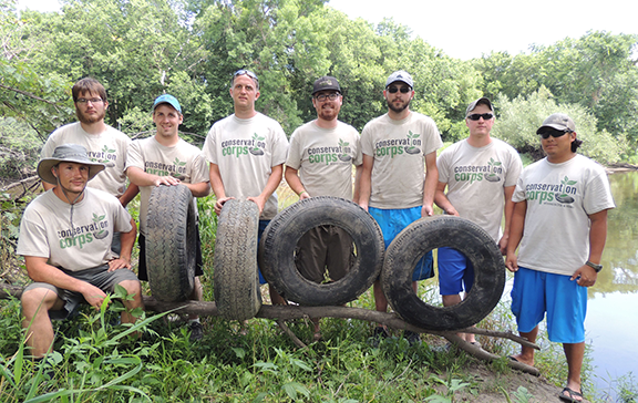 A Southern District crew showed off the some of the 1,100 tires pulled from the Cedar River since 2011. From left, Joe McCarthy, Derek Savage, Travis Wilder, Chris Kenow, Ben Schmall, David Ferris, Clinton Mercer and Mike Luke.