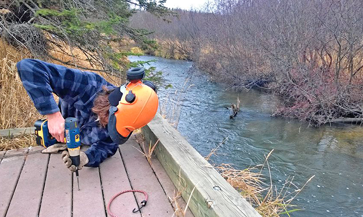 Crew member Jacob Wolf repaired a disability-accessible fishing platform on the Clearwater River near Bemidji.