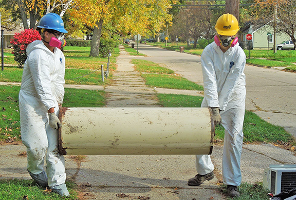 Corps members Jenna Strait (left) and Sara Anderson hauled a damaged water heater out of a Detroit home.