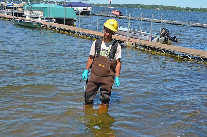 Crew member Anthony Wright sprayed flowering rush on the shoreline of Forest Lake.