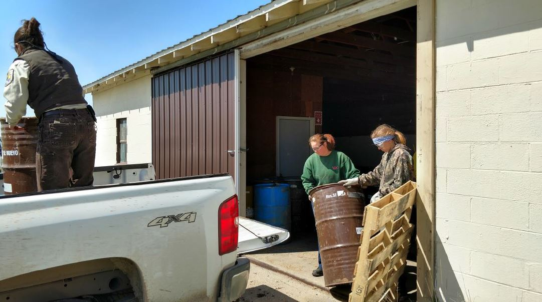 Lexie and Sarah help load barrels of seed into the back of Shilo's truck