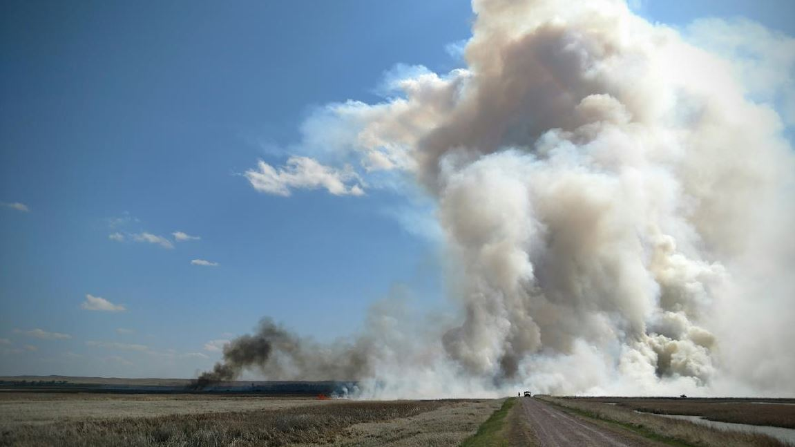 A smoke column rises above the burn unit