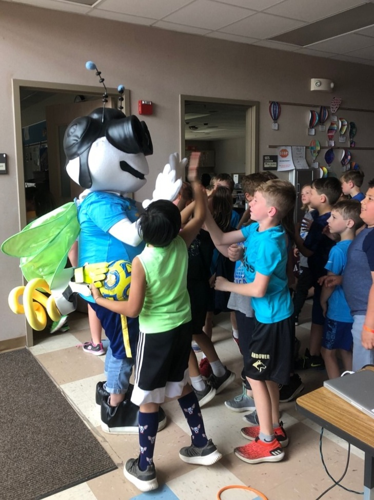 TOLBY giving high fives to a group of 3rd graders in Andover, MN.
