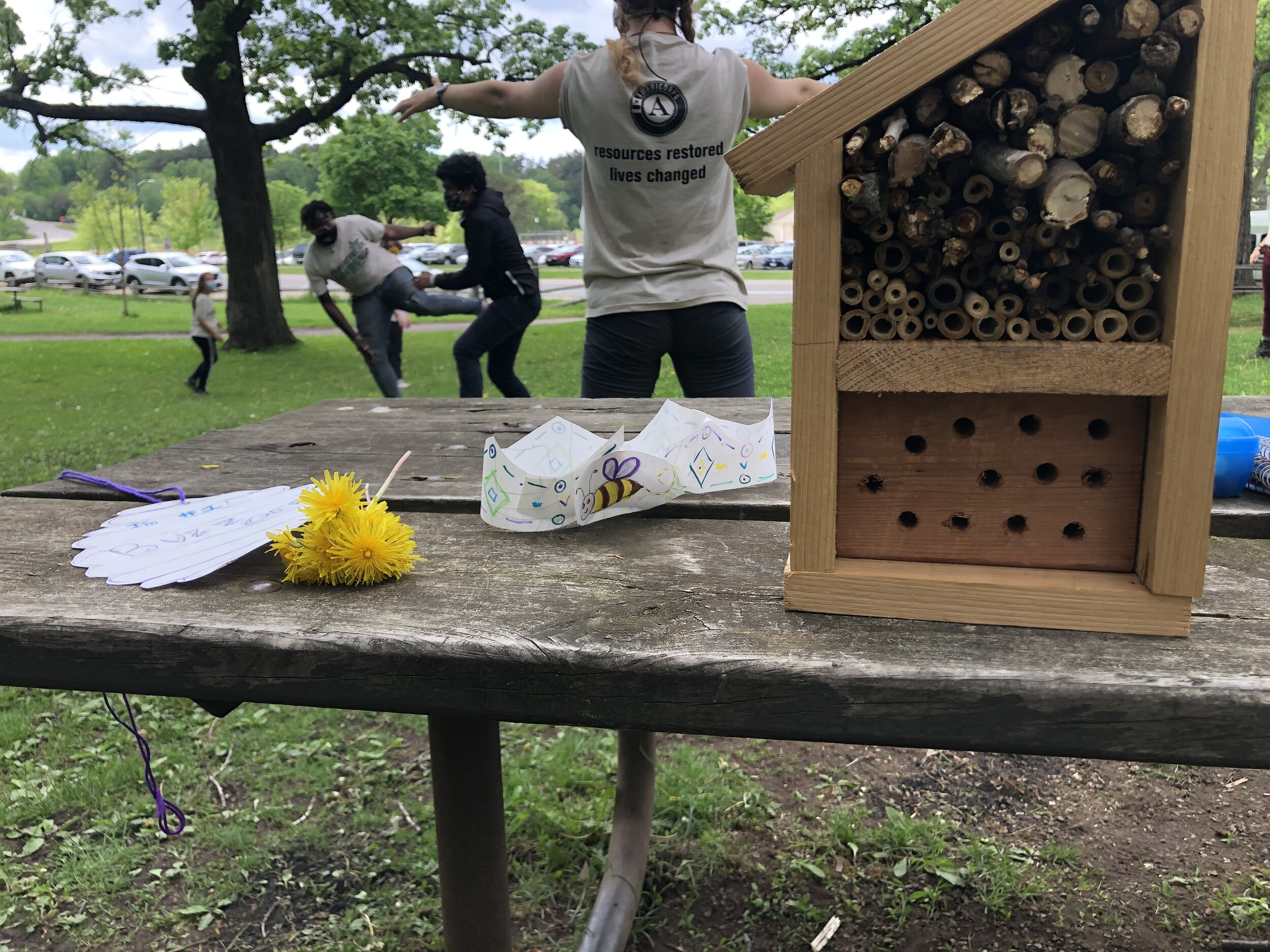 Youth playing a game of Buzzzzz in the background- where everyone is a Bee and if you are stung, or tagged, you are out. In the foreground sits our bee motel, paper bee crown, dandelion bouquet, and hive medal for the Bee Olympics winner.