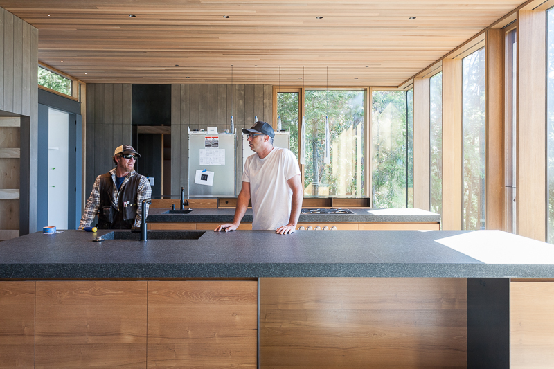 Lead carpenter Justin Sabala (L) and project manager Chad Rollins discuss finish details in the teak and alder kitchen, with an absolute granite counter top and a cedar slat ceiling.