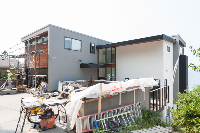 We've completed the exterior stucco siding and are applying the clear vertical grain cedar siding above the garage.