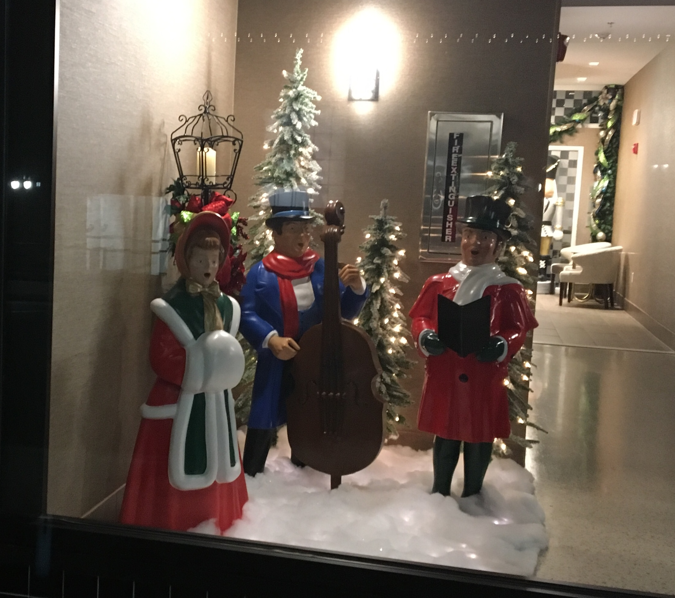 Fountain Street Entrance. Fiberglass scene of carolers, LED lights, faux snow and additional accessories.
