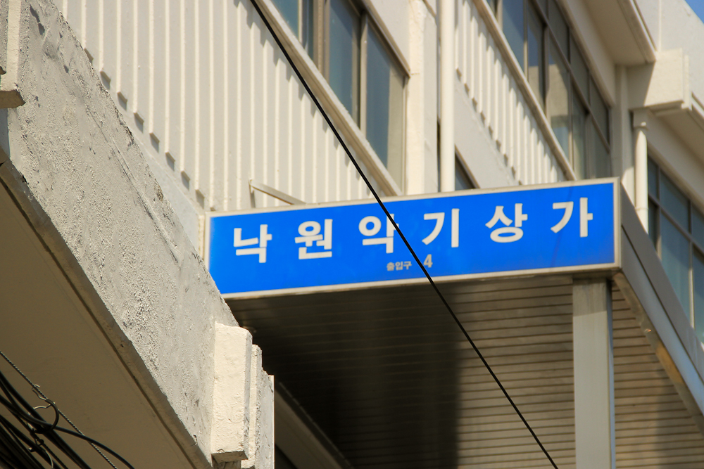 The sign that says Nakwon Arcade in korean.