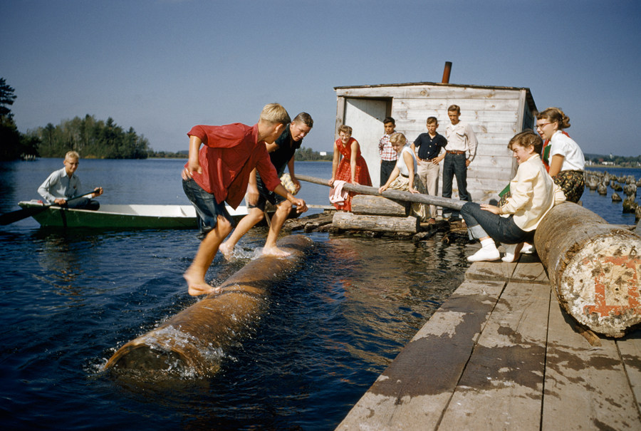 Sons of lumberjacks try to upset one another on rolling log in Hayward, Wisconsin, Feburary 1957.  PHOTOGRAPH BY VOLKMAR K. WENZTEL, NATIONAL GEOGRAPHIC