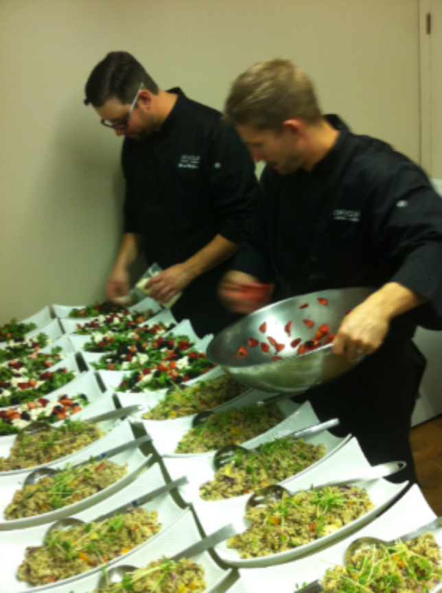 Platters being prepared before the salad course at a family-style dinner.