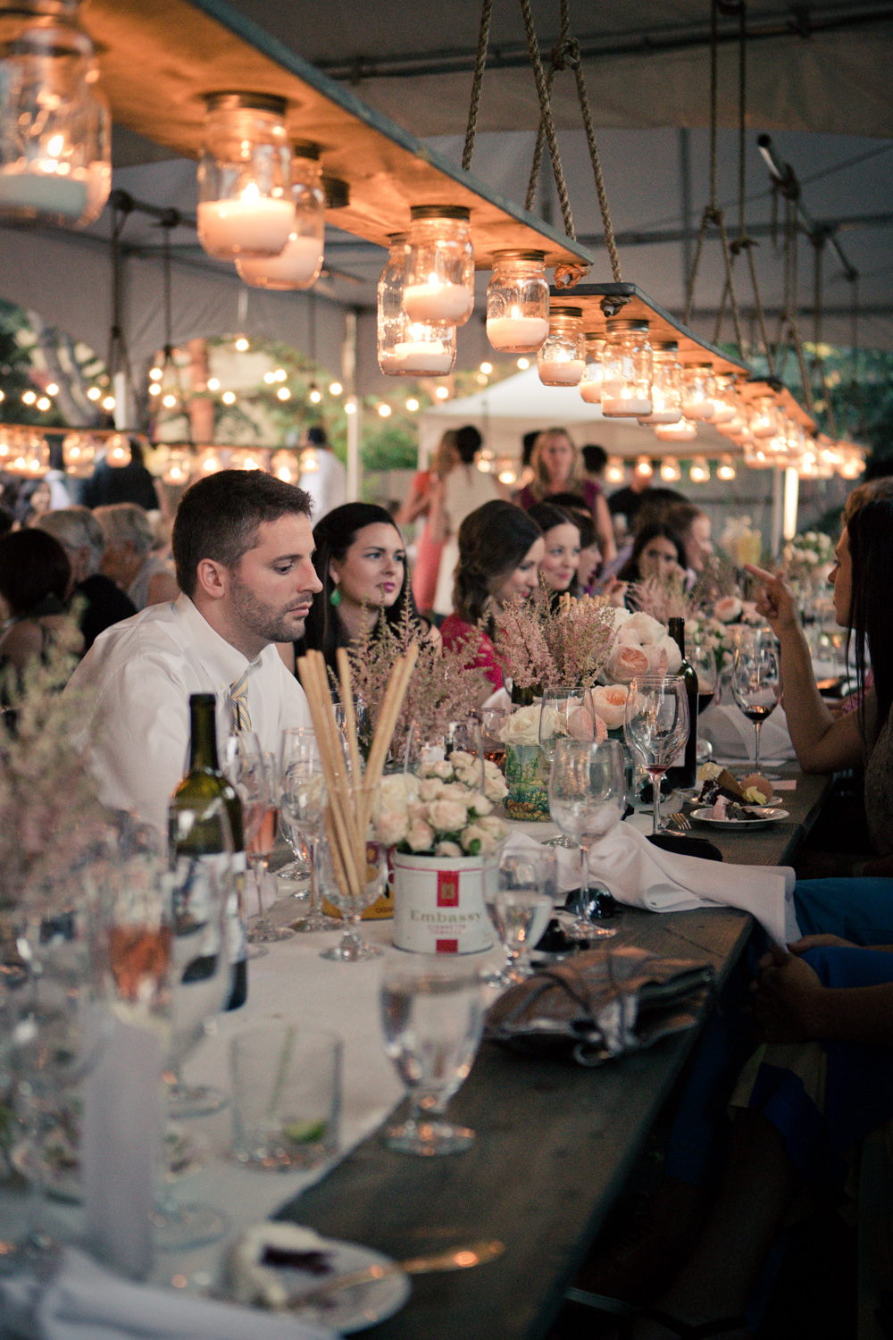 These custom made lantern chandeliers set the tone for this family-style tented wedding.