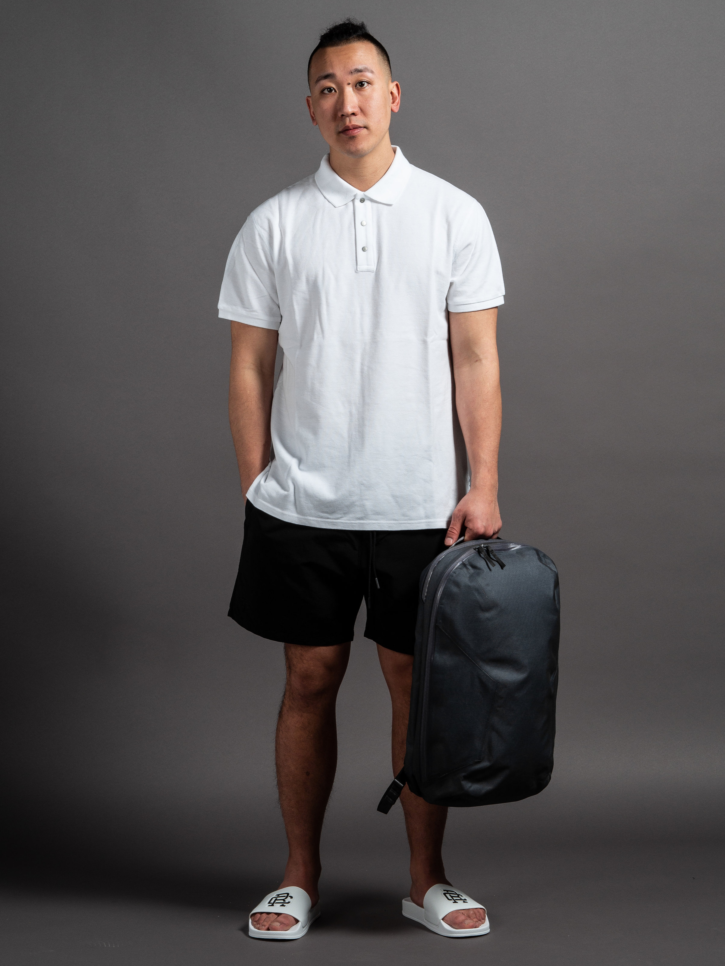 Reigning Champ Polo Tee  Reigning Champ Swim Shorts  Arc'teryx Veilance Nomin Pack  Reigning Champ Slides    SHOP THIS LOOK