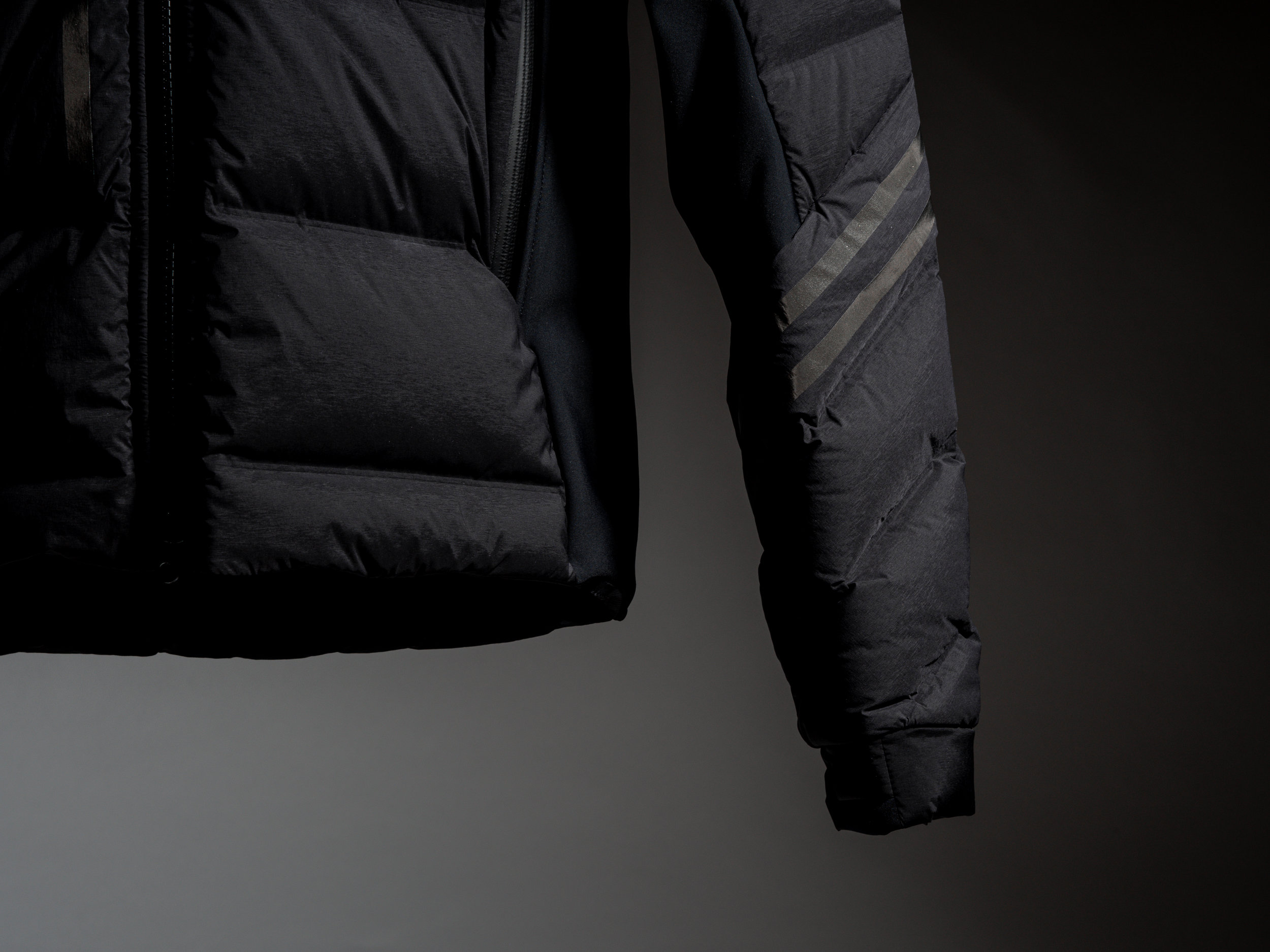 Canada Goose Hybridge CW Jacket - The Hybridge CW Jacket is filled with a lightweight down that seamlessly transitions its wearer between the unpredictable fall and winter months. It features stretch paneling on the shoulders, underarms, and side seams for improved comfort and mobility, as well as a stow hood and down fill in the collar for additional protection against the elements. It is finished with stylized reflective taping, and a Black Label patch. Canada Goose's down insulated outerwear is all Made in Canada.