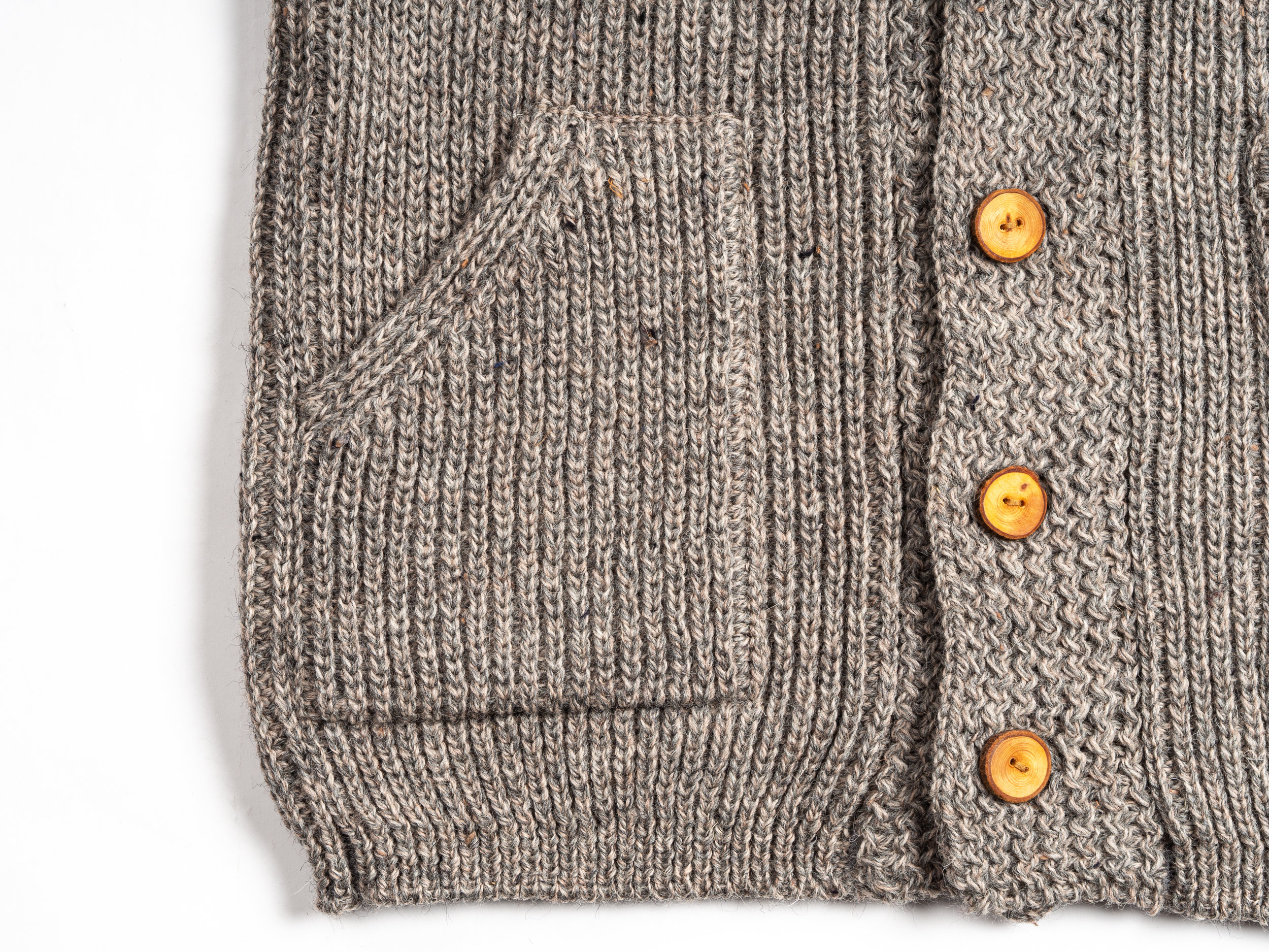18 Waits Wool Cardigans - The first delivery from 18 Waits includes two rustic hand knit wool cardigans. These sweaters are classic Canadiana, with a chunky knit wool body for warmth, raglan sleeves for an easy fit, hand sewn leather elbow patches for durability, and real Douglas Fir buttons for interest. The cardigans come with two patch hand pockets, and a shawl collar for added coziness. These sweaters are knit in a small, independent mill on Prince Edward Island.