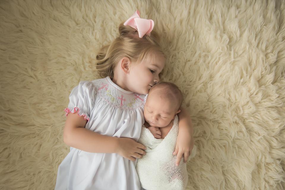 big sister kissing newborn