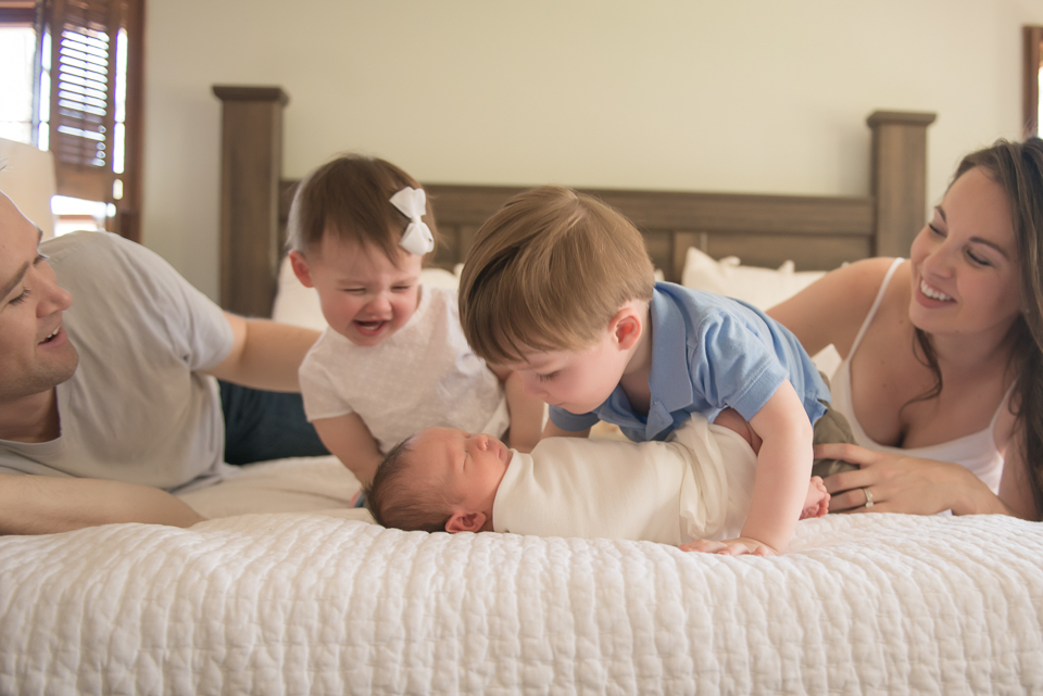 newborn and family playing on bed