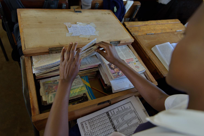 A student sorts her books during class at the Taranganya Girls School, Migori County.