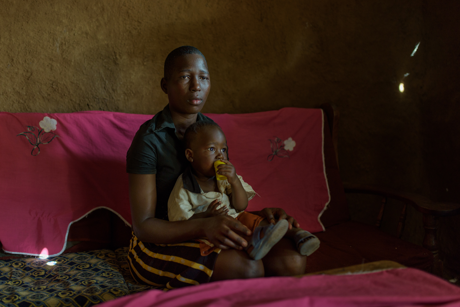 R.B., 17, with her three year old son B. at her parents home in Migori County. R. got pregnant after she finished primary school. Her parents were upset with her but pushed her to continue education. After giving birth to a son she went back to school. Her parents later told her that she was a burden and asked her to drop out of school. R. has been home since then and hopes to go back to school someday.