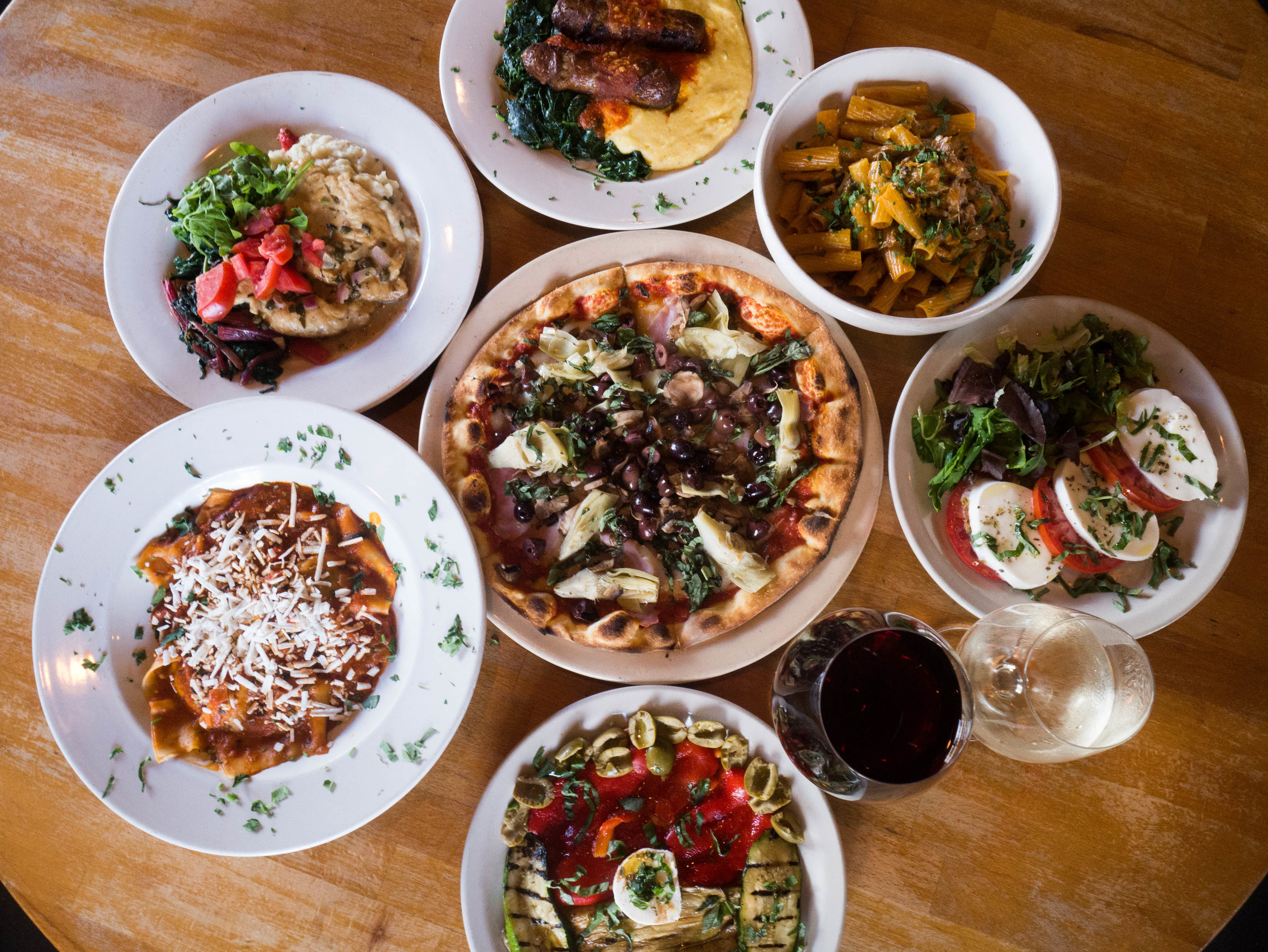 Plates of assorted Italian dishes including pizza, pasta, and salad