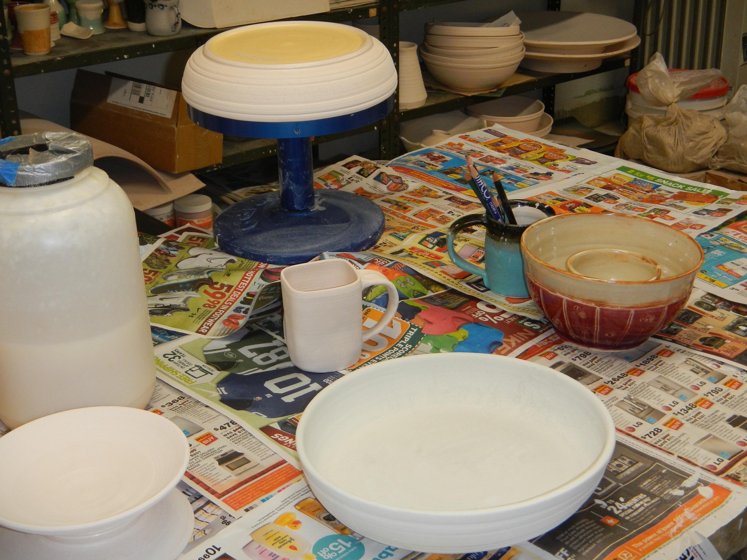 brushing wax resist on pot feet before glazing