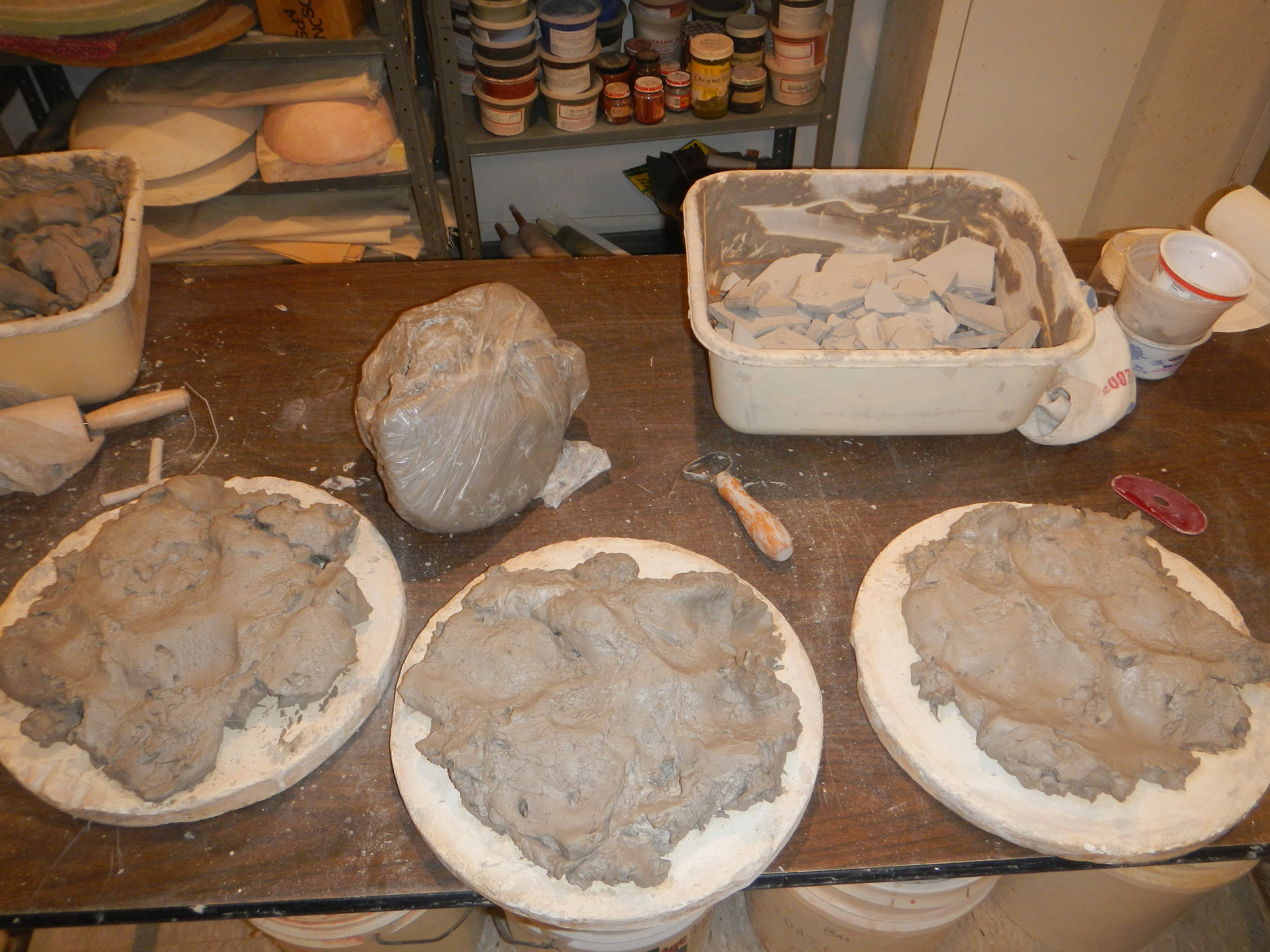 Slaked clay firming up a bit on plaster, nearly ready to wedge. More slaked clay in basins, not seen in the picture, to be spread on batts after this batch and the next batch and... (And more dry clay scrap already building up, in the background.)