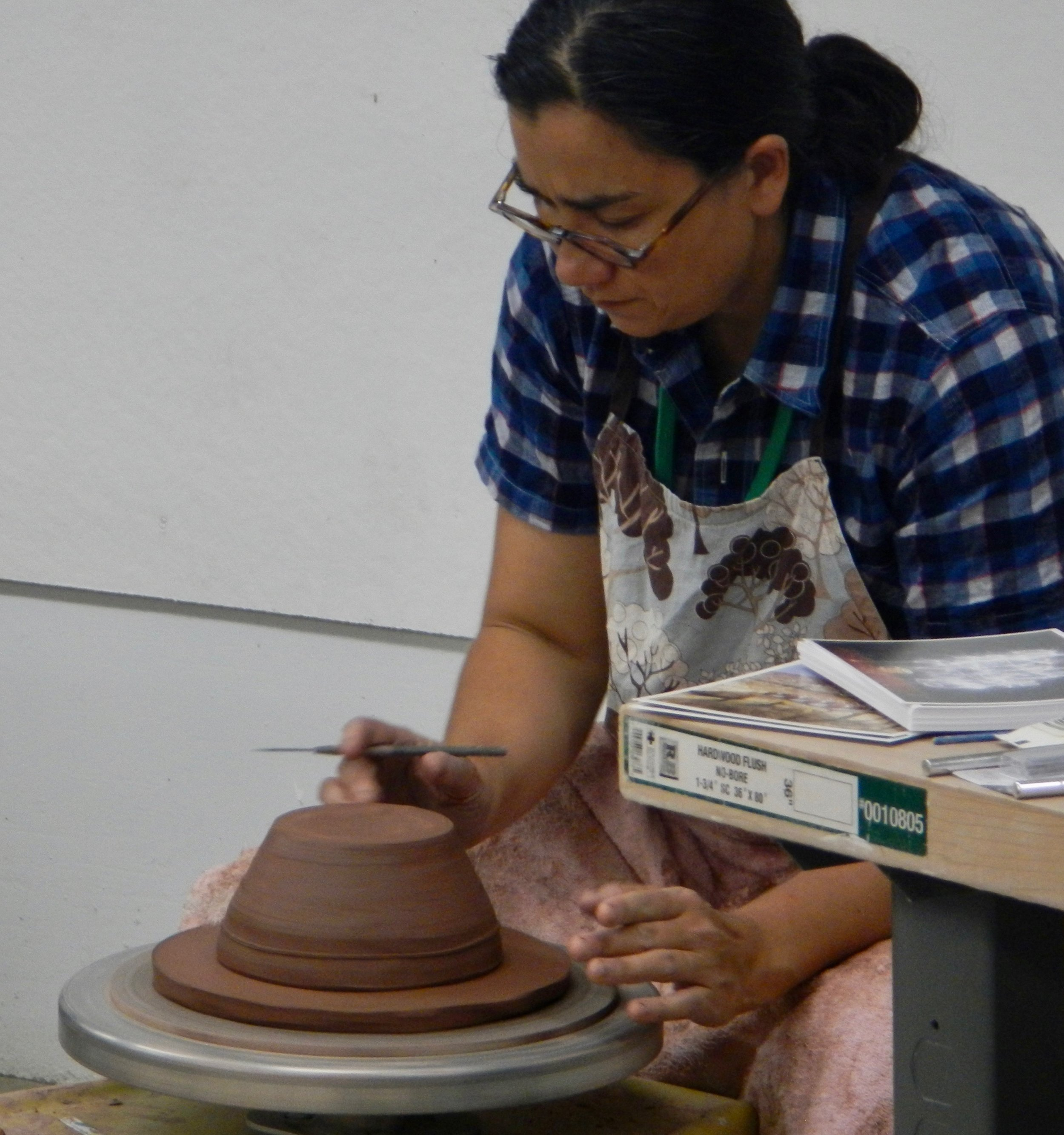 (Turning over the bowl on a freshly thrown pad of clay to trim a foot.)