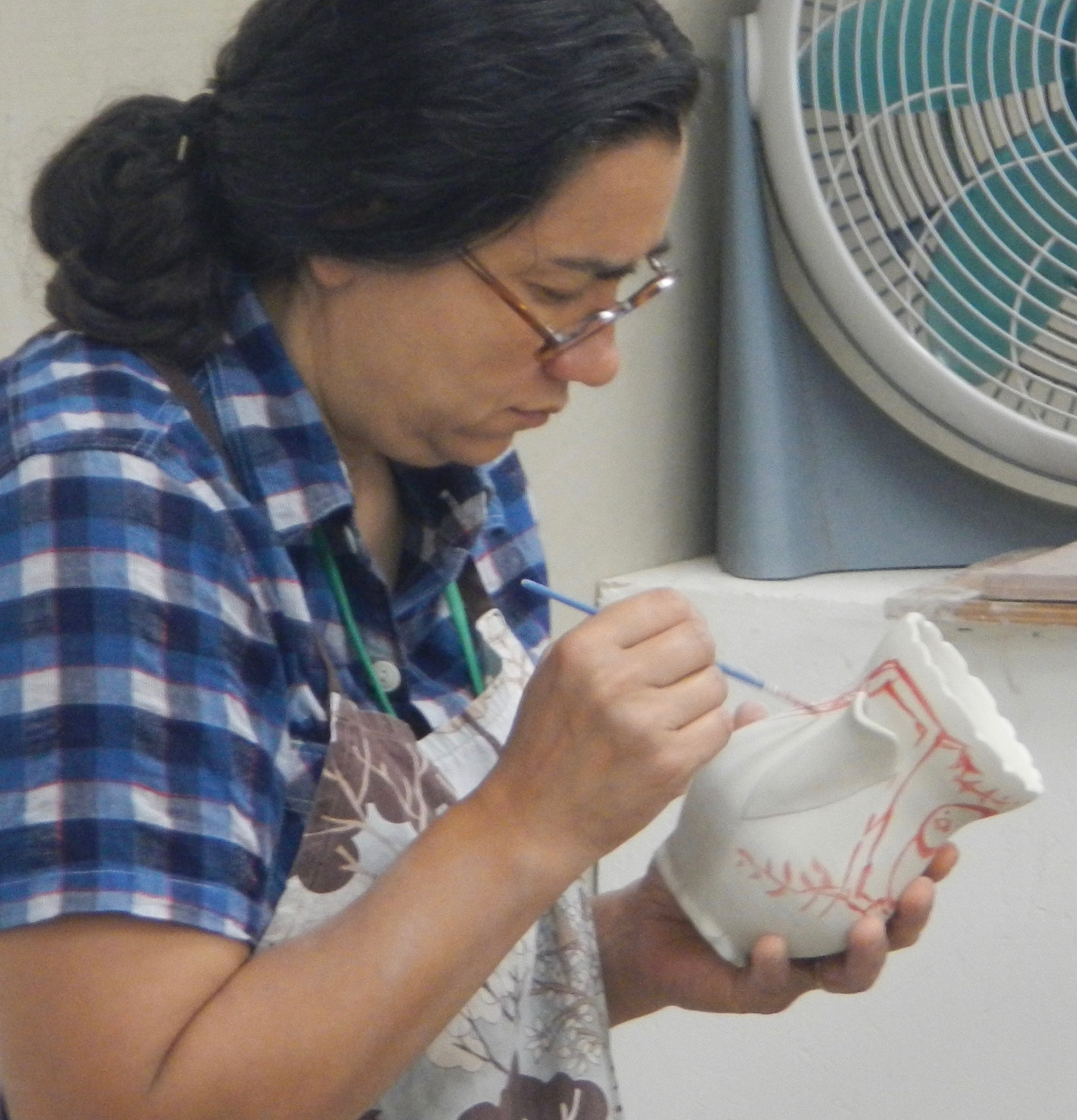 (Ayumi applying luster (like the lustered bird in the previous photo)over a glaze-fired white pot)