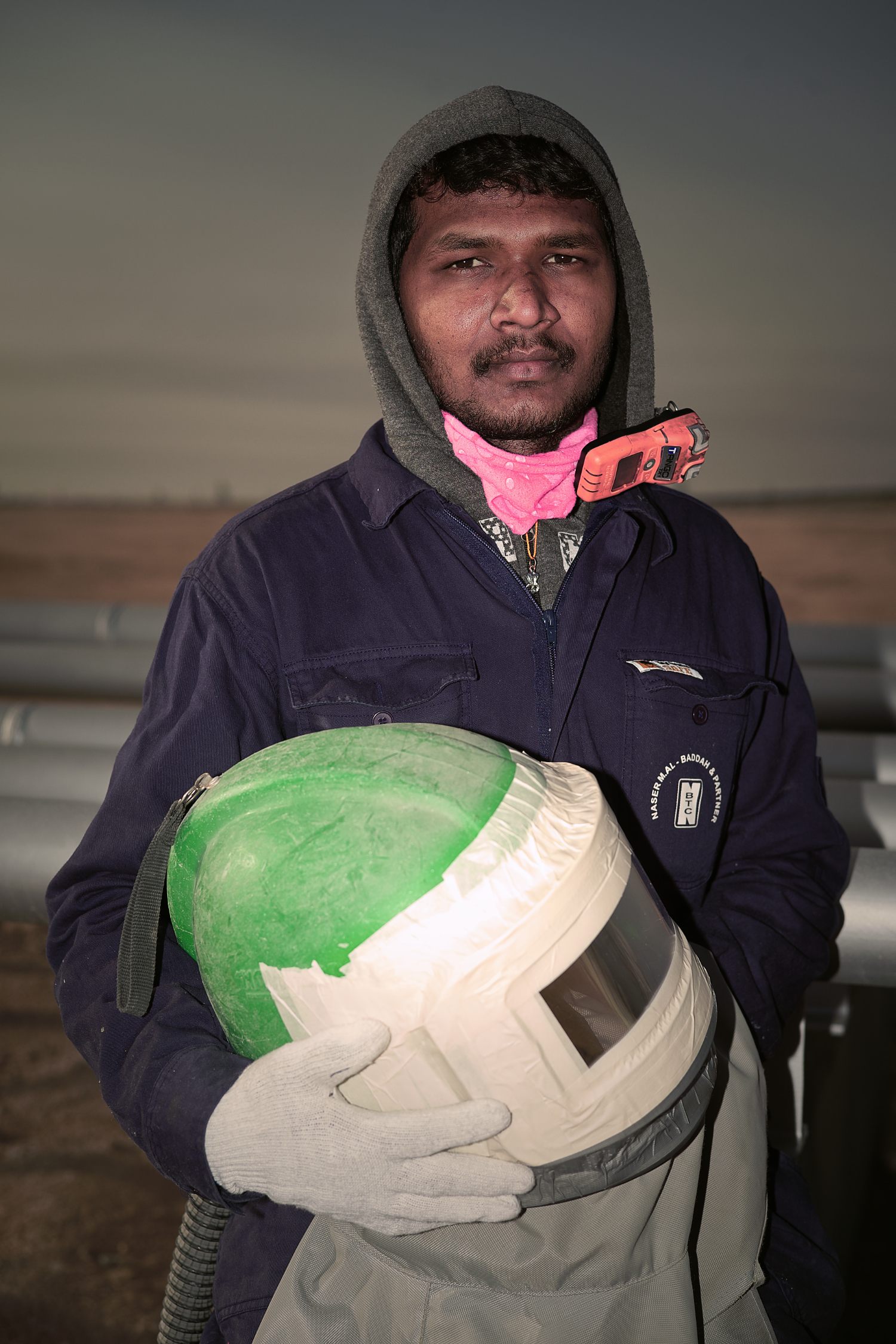 Dasharath Humnabade, 22 y/o, Painter/Grit Blaster   Dasharath is from Ghaborael, India. He left home at 18 to support his family income which currently comes from farming. His ambition is to do the best he can and one day be a Supervisor.  The orange device near his chin is a carbon monoxide monitor used to make sure that the air coming inside the helmet is safe to breath.