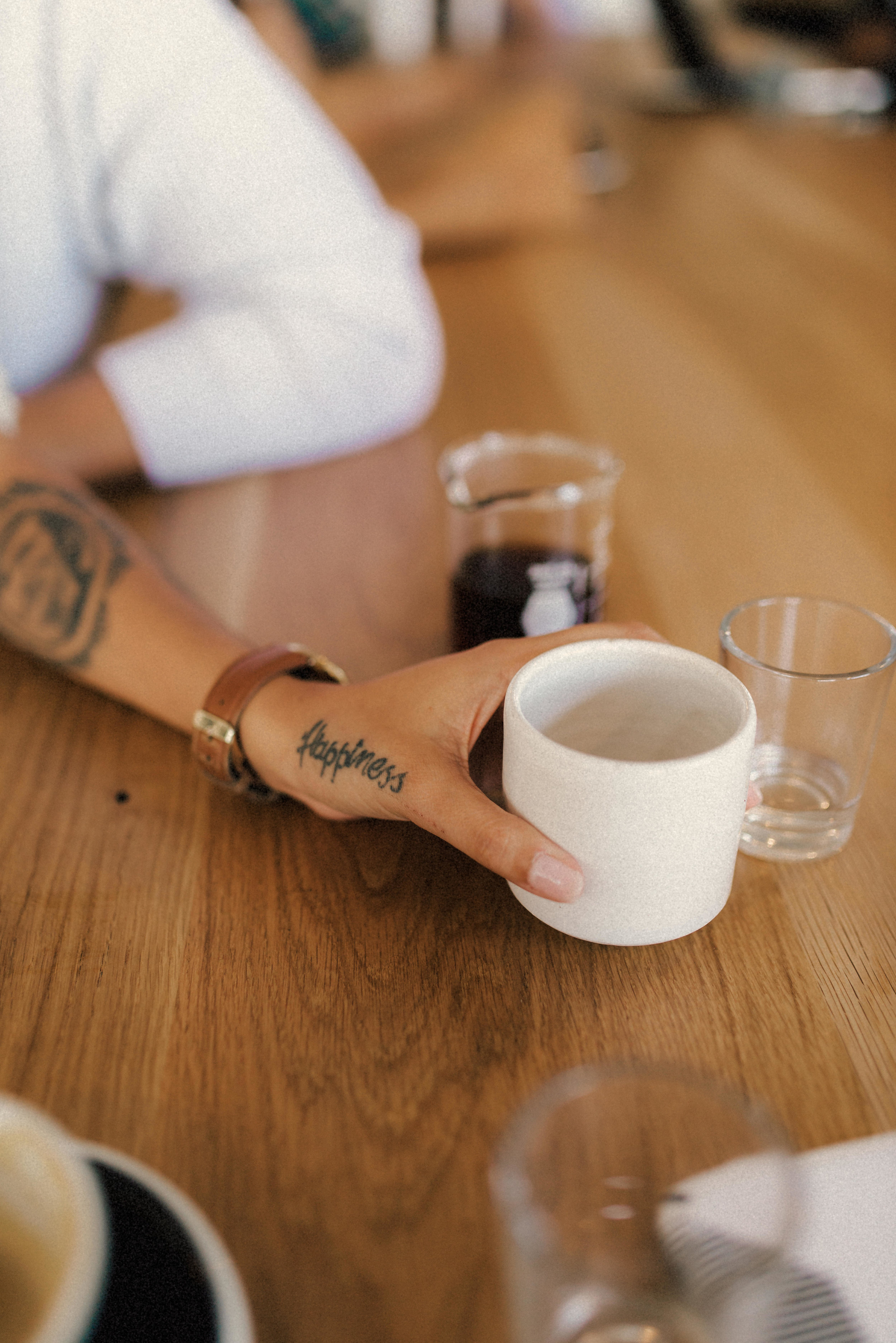 a tattoo on Hillary's hand as she reaches for her coffee - Bandit Coffee - St Pete Florida - Naples Florida Wedding Photographer - Tampa Wedding Photographer