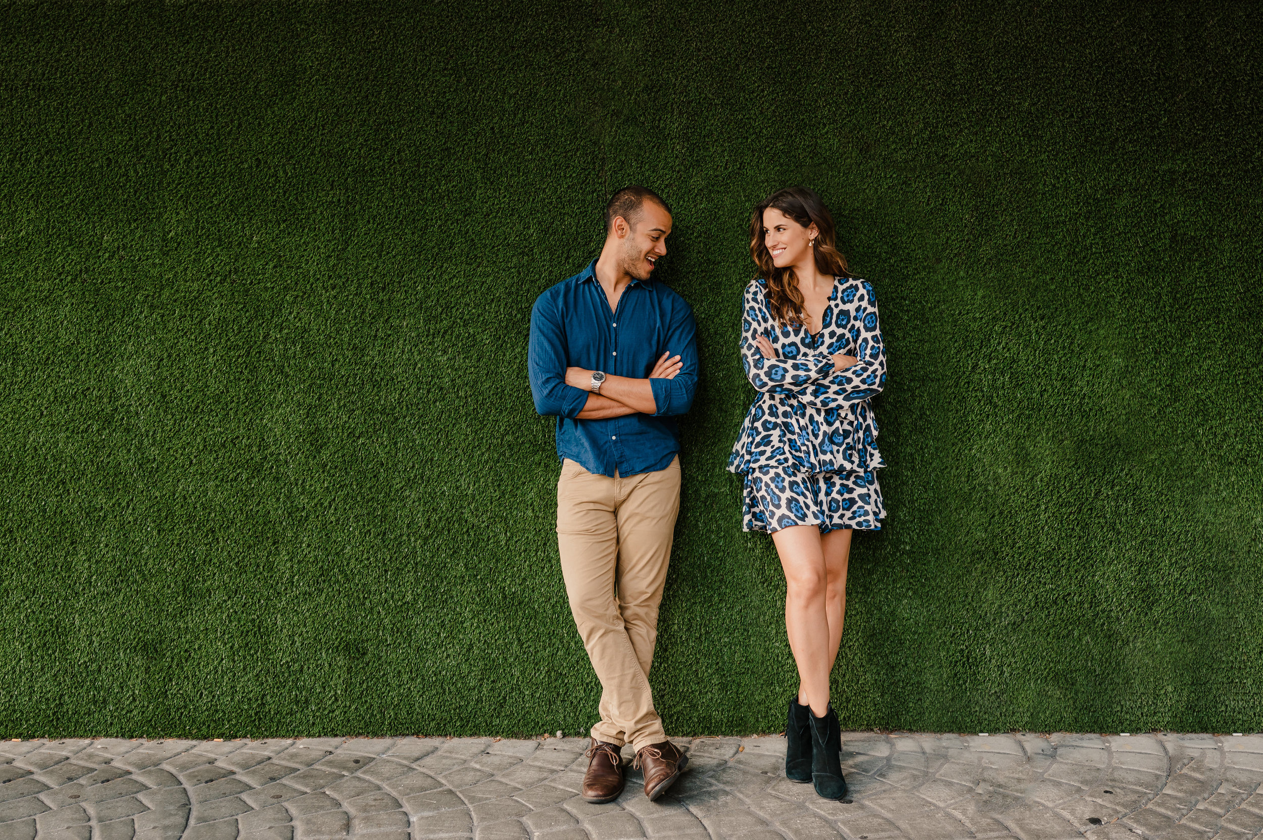 Andres and Rebecca posing in front of green wall in Downtown Tampa Florida